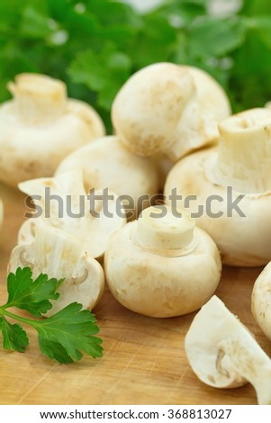 Raw mushrooms with greens on the table - stock photo