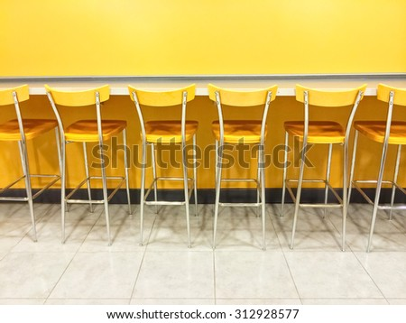 Raw of empty yellow chairs in a cafeteria. - stock photo