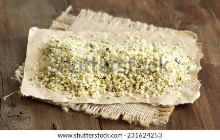 Raw organic hemp seeds on a wooden table - stock photo