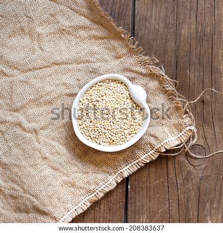 Raw Organic Quinoa grain in a bowl on wooden table - stock photo