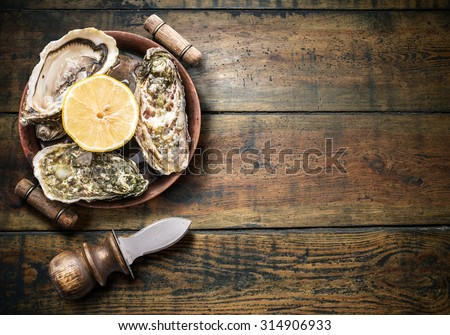 Raw oysters on the old wooden table. - stock photo