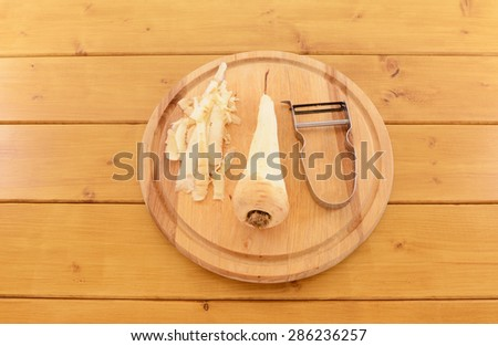 Raw parsnip being peeled with vegetable peeler on a wooden chopping board - stock photo