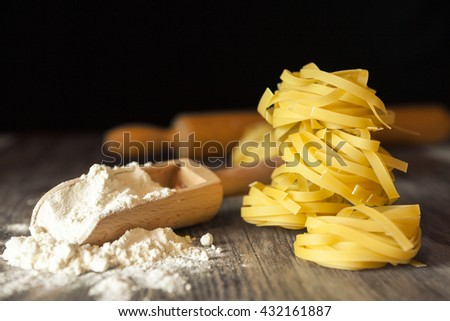Raw pasta and flour in a wooden scoop - stock photo