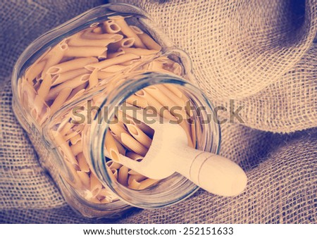 Raw pasta in a glass bowl. Vintage retro effect. - stock photo