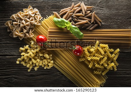 Raw pasta with basil and tomato overhead shoot - stock photo