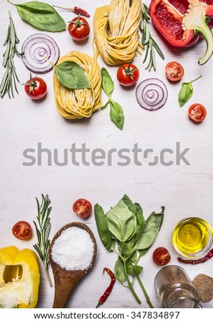 raw pasta with colorful various of organic farm vegetable, wooden spoon, butter and herbs place for text,frame on wooden rustic background top view close up - stock photo