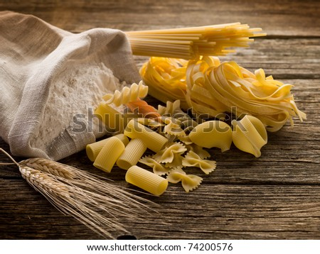 raw pasta with ears and flour on wood background - stock photo
