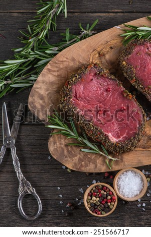 Raw peppered steak with herbs on wooden table - stock photo