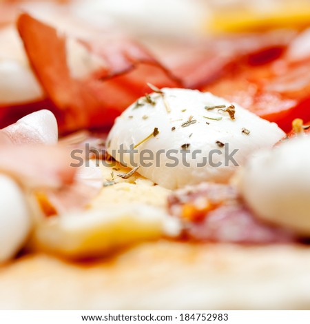Raw pizza dough with mozzarella and proscuitto on top - stock photo