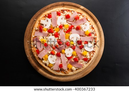 raw pizza on a dark background with ham, mushrooms, cheese and sweet pepper top view - stock photo