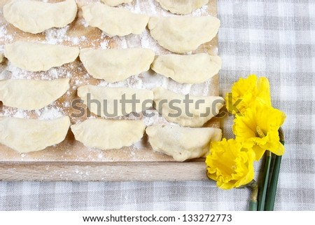 Raw polish dumplings lying on checked table cloth, yellow daffodils in background - stock photo