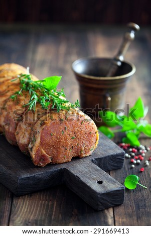 Raw pork loin, herb and spices marinade on cutting board, selective focus - stock photo