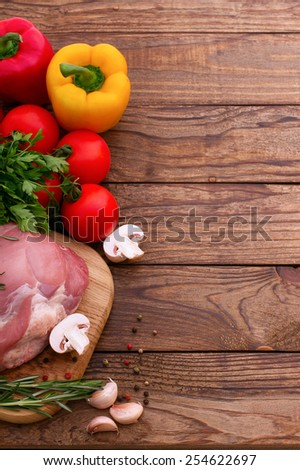 Raw pork meat with spices and vegetables on wooden table - stock photo
