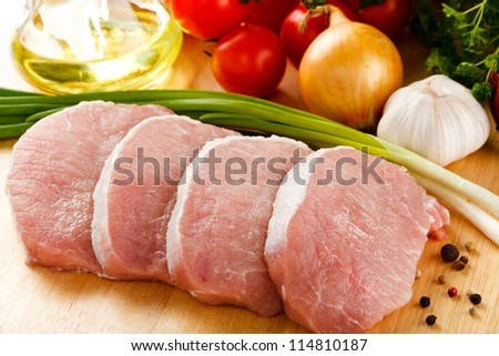 Raw pork on cutting board and vegetables - stock photo