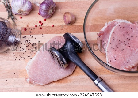 Raw pork schnitzel, garlic, pink pepper and seeds of brown Indian mustard on wooden board with meat tenderizer. Raw pork schnitzel in glass bowl. - stock photo