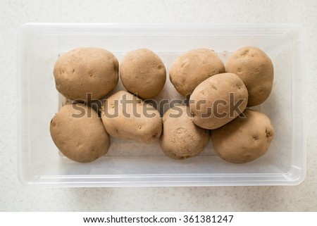 Raw potatoes in a plastic container. - stock photo