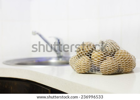 Raw potatoes in a sack at kitchen table. - stock photo