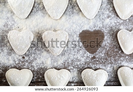 Raw ravioli in the shape of hearts, sprinkle with flour, on wooden background closeup. Cooking dumplings. Top view. - stock photo
