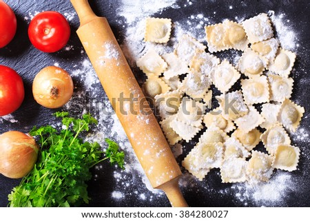 Raw ravioli with vegetables on dark board - stock photo
