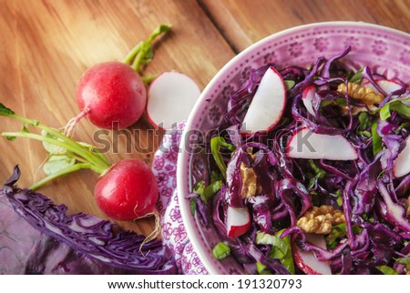 Raw red cabbage salad with radish, basil and walnut, wooden table - stock photo