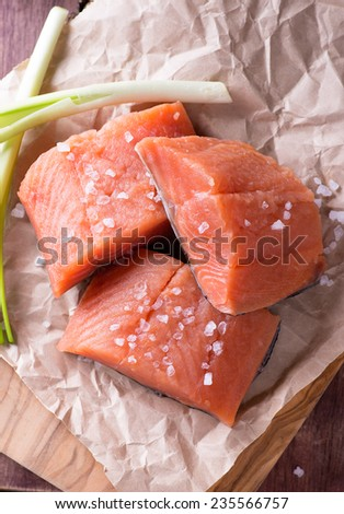 Raw red fish fillet with sea salt over wooden board, selective focus, top view - stock photo