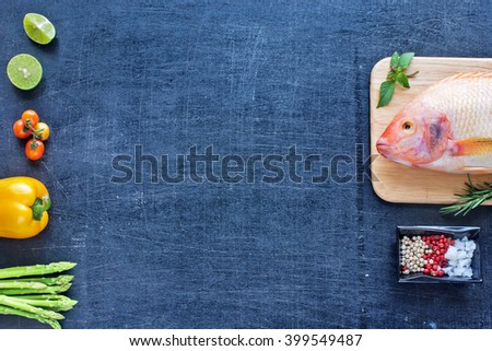 Raw red fish (Nile tilapia) on a wooden board with vegetables, lime, herbs and spices. Dark background. Space for text.  - stock photo