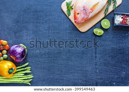 Raw red fish (Nile tilapia) with lime, herbs, spices and fresh vegetables. Dark background. Copy space.  - stock photo