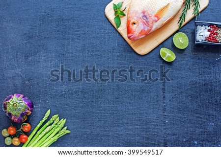 Raw red fish (Nile tilapia) with lime, herbs, spices and fresh vegetables on a dark wooden board. Copy space.  - stock photo