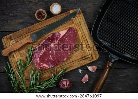 Raw rib eye beef steak with herbs and spices from above on wooden rustic table - stock photo