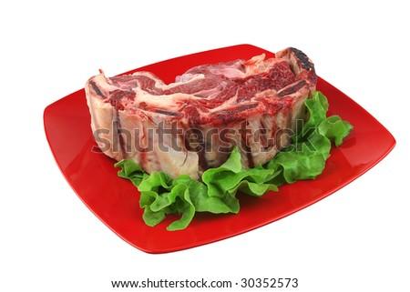raw rib's and salad on red dish - stock photo