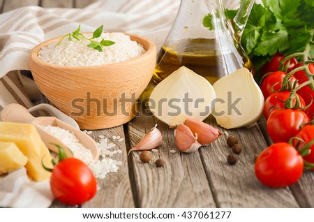 Raw rice and ingredients for cooking risotto, rustic background, selective focus - stock photo