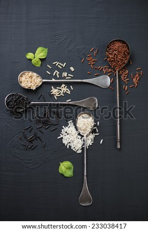 Raw rice kernels of different types over black wooden background - stock photo