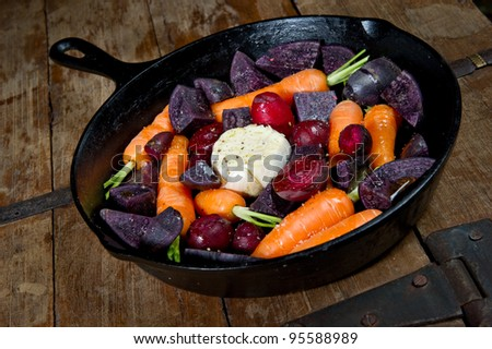Raw root vegetables in a cast iron skillet ready for the oven. Vegetables include carrots, red beets, garlic and purple potatoes. - stock photo