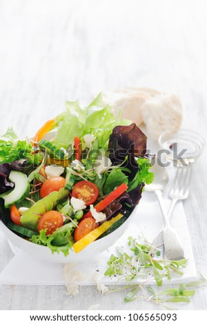 Raw salad with green lettuce, tomato, feta, peppers, olives and cucumber in a bowl with cutlery - stock photo
