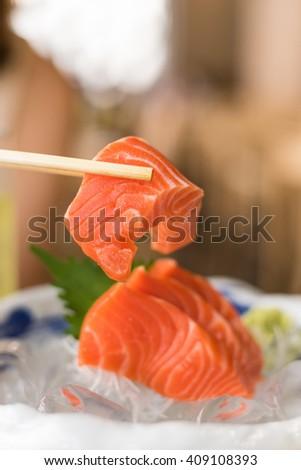 Raw Salmon in the chopsticks - stock photo