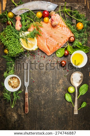 Raw salmon preparation for cooking on rustic wooden background with fresh ingredients , fork and spoon, top view, place for text. - stock photo