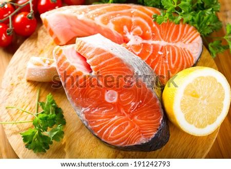 raw salmon steak on wooden board - stock photo