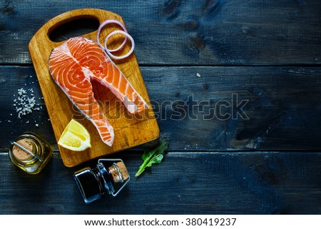 Raw salmon steak with fresh seasoning and spices on rustic wooden background, top view, banner for website with cooking concept. - stock photo