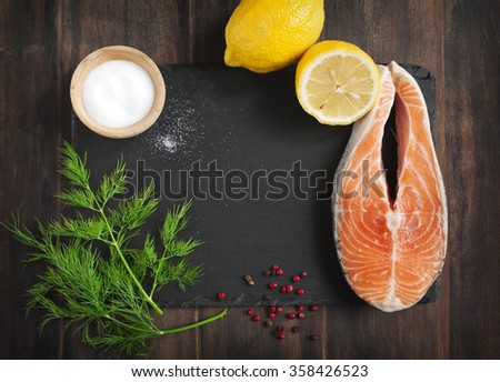 Raw salmon steak with herbs and lemon on black board - stock photo