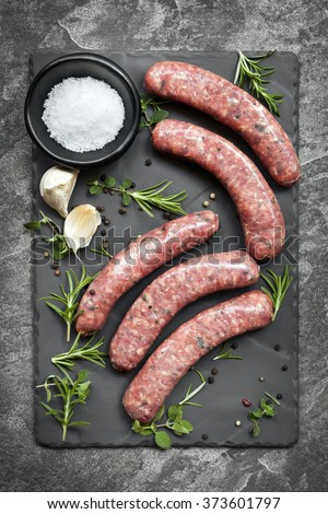 Raw sausages on slate, with herbs and spices.  Overhead view. - stock photo