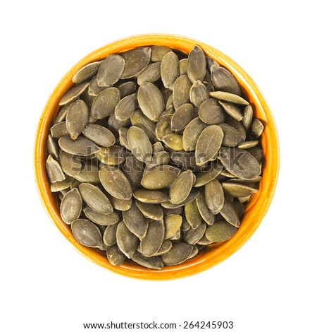 Raw shelled pumpkin seeds in orange bowl isolated and viewed from directly above. - stock photo
