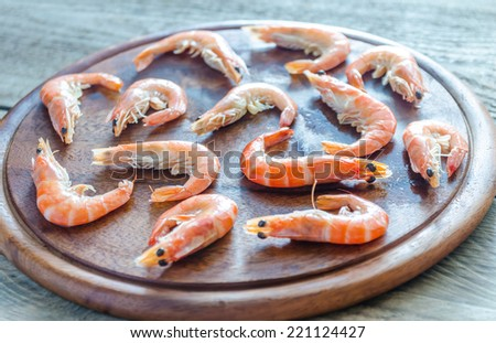 Raw shrimps on the wooden board - stock photo