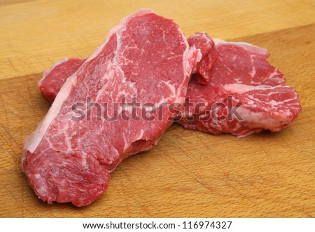 Raw sirloin steaks on wooden chopping board - stock photo