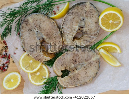 Raw sliced steaks of sturgeon with lemon, dill and spices. Shallow depth of field  - stock photo