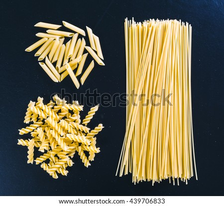 Raw spaghetti on black wooden background, top view - stock photo