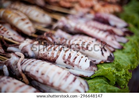Raw squid barbeque skewer. Traditional thai cuisine. - stock photo