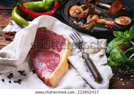 Raw steak in textile served with vegetables and forest mushrooms over old wooden table. See series - stock photo