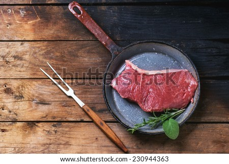Raw steak in vintagev pan over old wooden table. Top view. - stock photo