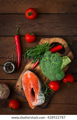 Raw steak salmon and vegetables for cooking on wooden background. Dietary menu. Proper nutrition. Top view - stock photo