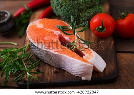 Raw steak salmon and vegetables for cooking on wooden background in a rustic style.  Dietary menu. Proper nutrition. - stock photo